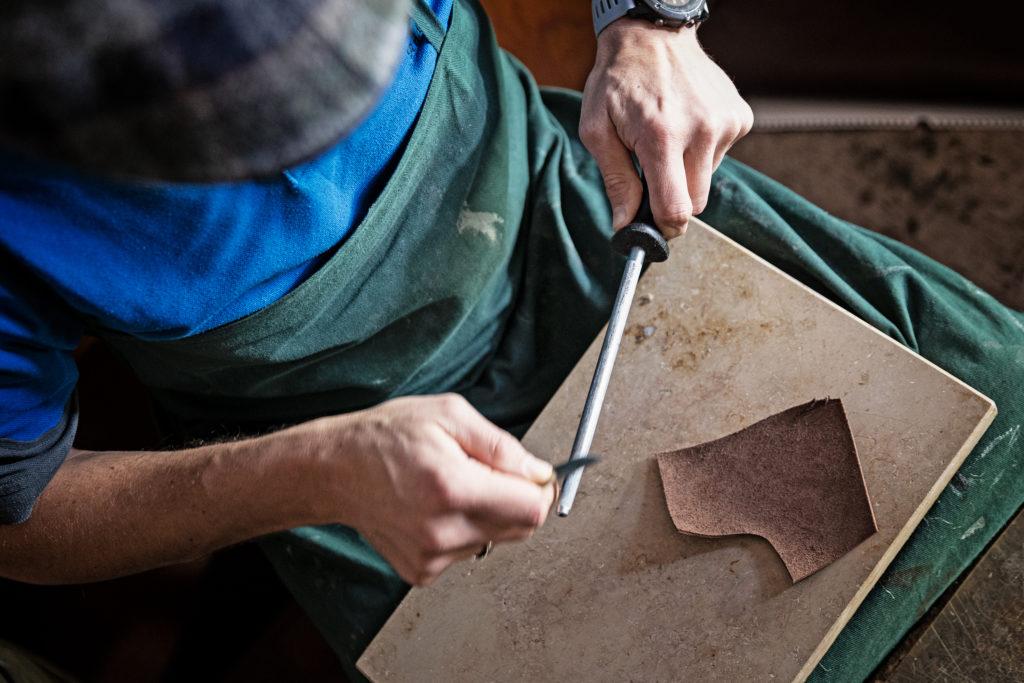 Handwerker schleift ein Meser von Hand.