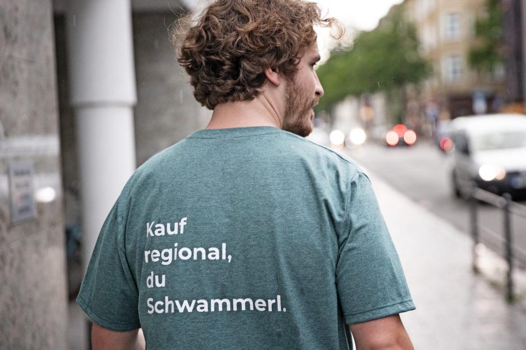 """Mann im T-Shirt mit der Aufschrift """"Kauf regional, du Schwammerl."""""""